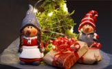 Two small santas with the christmas presents and the christmas tree.